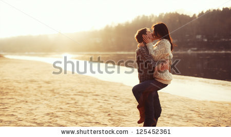 stock-photo-young-beautiful-couple-in-love-staying-and-kissing-on-the-beach-on-sunset-soft-sunny-colors-125452361